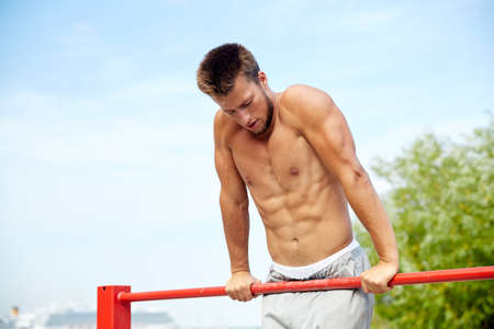grapple: fitness, sport, training and lifestyle concept - young man exercising on horizontal bar outdoors