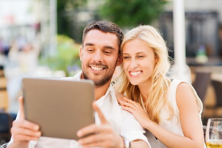 viewing: love, dating, people, technology and holidays concept - happy couple with tablet pc computer and glasses of wine at restaurant lounge or terrace Stock Photo