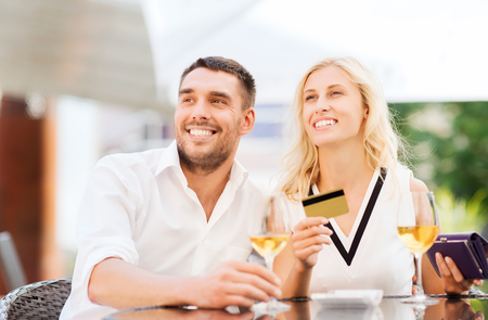 date, people, payment and relations concept  - happy couple with credit card, bill and wine glasses at restaurant terrace Stock Photo