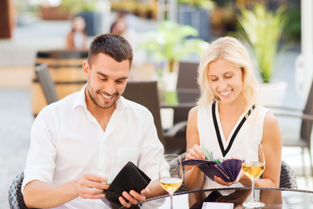 paying money: date, people, payment and financial independence concept - happy couple with cash money in wallets and wine glasses paying bill at restaurant