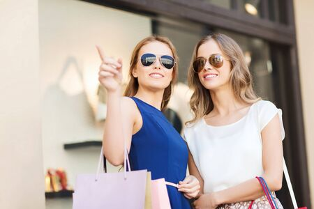 lifestyle shopping: sale, consumerism and people concept - happy young women with shopping bags pointing finger at shop window in city Stock Photo