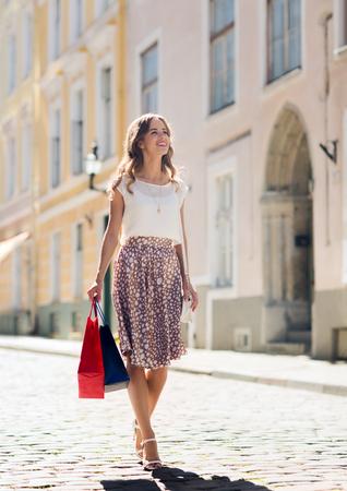 Verkauf, Konsum und Menschen Konzept - glückliche junge Frau mit Einkaufstüten entlang Stadt Straße Standard-Bild