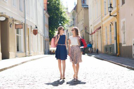 Verkauf, Verbraucherschutzbewegung und Leutekonzept - glückliche junge Frauen mit den Einkaufstaschen, die entlang Stadtstraße gehen Standard-Bild