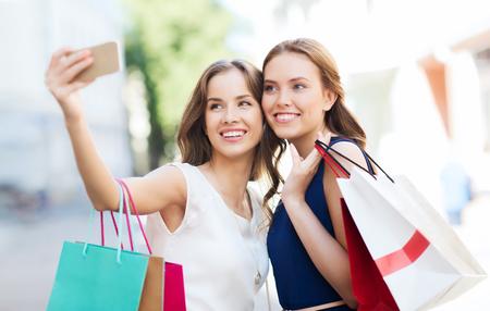 販売、消費、技術と人のコンセプト - ショッピング バッグやスマート フォンの通り市に selfie を取って幸せな若い女性