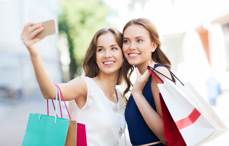 young women: sale, consumerism, technology and people concept - happy young women with shopping bags and smartphone taking selfie on city street Stock Photo