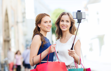 sale, consumerism, technology and people concept - happy young women with shopping bags and smartphone selfie stick taking picture on city street Stock Photo
