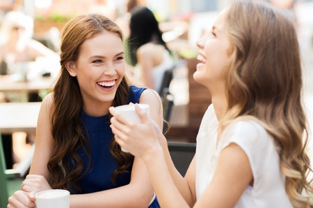 drink coffee: communication and friendship concept - smiling young women with coffee cups at cafe