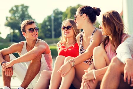 group of friends: friendship, leisure, summer and people concept - group of smiling friends sitting on city street Stock Photo