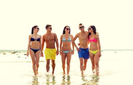 pareja de adolescentes: friendship, sea, summer vacation, holidays and people concept - group of smiling friends wearing swimwear and sunglasses walking on beach