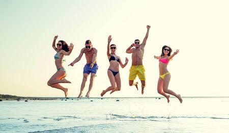 traje de baño: amistad, el mar, las vacaciones de verano, las vacaciones y la gente concepto - grupo de amigos sonrientes que usan trajes de baño y gafas de sol salta en la playa Foto de archivo