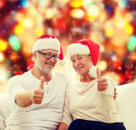 old man happy: family, holidays, christmas, age and people concept - happy senior couple in santa helper hats sitting on sofa over red lights background and showing thumbs up gesture Stock Photo