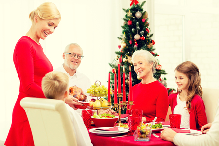 christmas dish: family, holidays, generation, christmas and people concept - smiling family having dinner at home