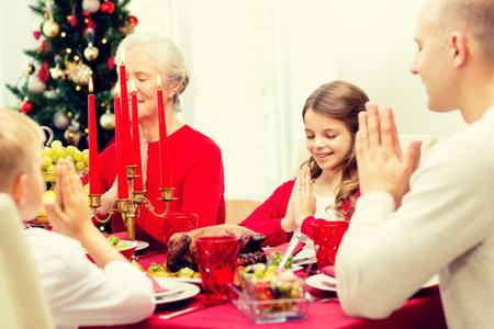family praying: familiares, vacaciones, generaci�n, Navidad y la gente concepto - sonriendo familia cenando y orando en casa Foto de archivo