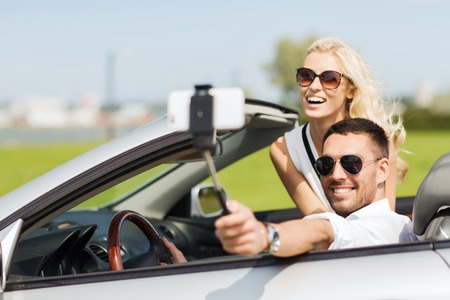 Road Trip, les loisirs, en couple, la technologie et les gens le concept - homme heureux et femme de conduire en voiture cabriolet et prendre des photos avec smartphone sur selfie bâton