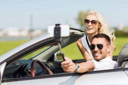 Straße Reise, Freizeit, Paar, Technologie und Menschen Konzept - glücklicher Mann und Frau in Cabrio Auto fahren und mit dem Smartphone auf selfie-Stick, die Foto