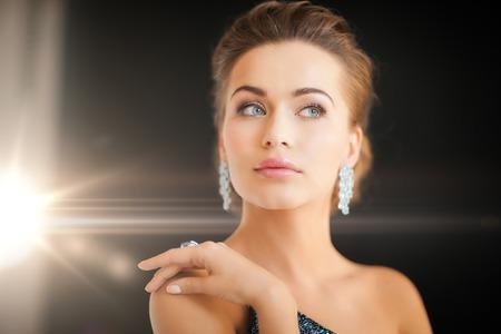 mujeres fashion: mujer hermosa en vestido de noche que llevaba aretes de diamantes Foto de archivo