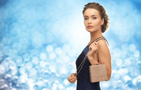 mujer elegante: La gente, las vacaciones, el lujo y el concepto de glamour - mujer en vestido de noche con bolsa pequeña sobre fondo luces azules