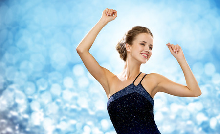dancing woman: people, party, holidays and glamour concept - smiling woman dancing with raised hands over blue lights background