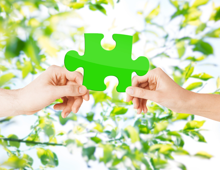 natural energy: nature, ecology, energy saving, people and environment concept - close up of couple hands with green puzzle over natural background