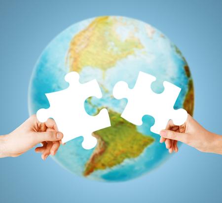 Ökologie, Energieeinsparung, Menschen und Umwelt-Konzept - auf blauem Hintergrund Nahaufnahme von Paar Hände, die versuchen weiß Puzzleteile über der Erde Globus zu verbinden