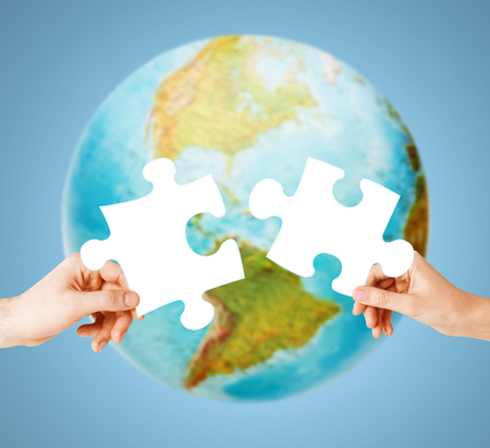 ecology, energy saving, people and environment concept - close up of couple hands trying to connect white puzzle pieces over earth globe on blue background
