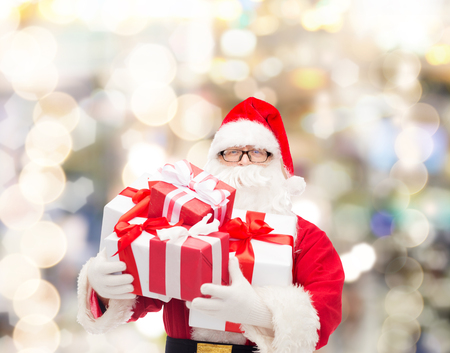 christmas costume: christmas, holidays and people concept - man in costume of santa claus with gift boxes over lights background