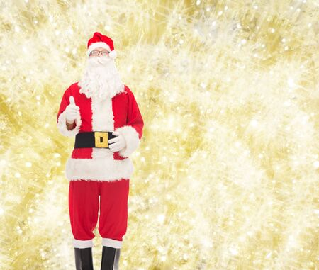 christmas costume: christmas, holidays, gesture and people concept- man in costume of santa claus showing thumbs up over yellow lights background Stock Photo