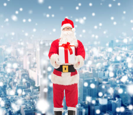 snow man party: christmas, holidays and people concept - man in costume of santa claus with gift box over snowy city background