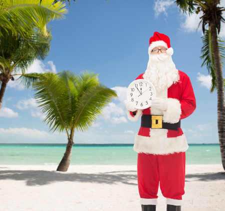 12 oclock: christmas, holidays, travel and people concept - man in costume of santa claus with clock showing twelve over tropical beach background