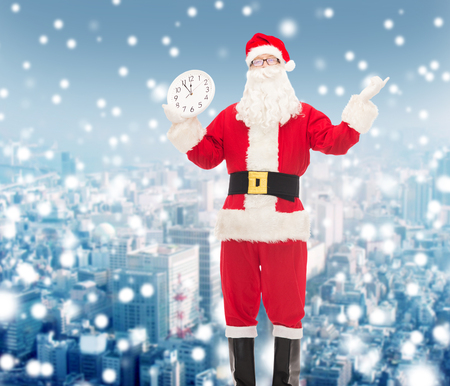 12 oclock: christmas, holidays and people concept - man in costume of santa claus with clock showing twelve over snowy city background