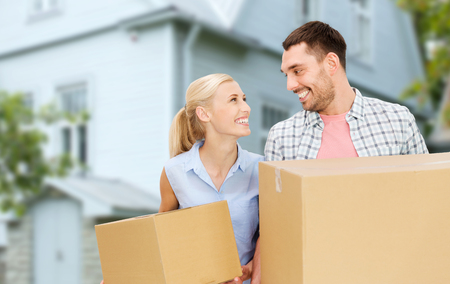 relocating: home, people, repair and real estate concept - happy couple holding cardboard boxes and moving to new place Stock Photo
