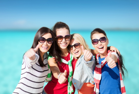 summer holidays, vacation and people concept - happy teenage girls in sunglasses or young women showing thumbs up over beach background