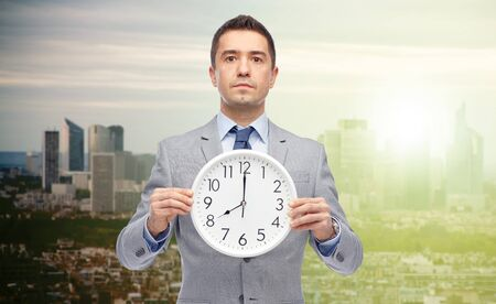 o'clock: business, people, time management and work concept - businessman in suit holding clock showing 8 oclock over sunrise city background Stock Photo