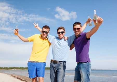 nonalcoholic beer: summer holidays, vacation, people and bachelor party concept - group of happy male friends having fun and drinking beer on beach