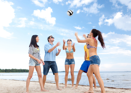 family playing: summer holidays, sport, leisure and people concept - group of happy friends playing beach ball