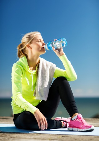 water sports: fitness and lifestyle concept - woman drinking water after doing sports outdoors