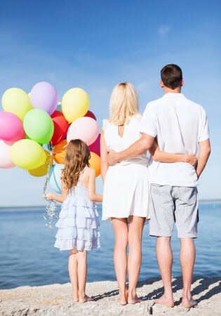 mum and daughter: summer holidays, celebration, children and people concept - happy family at the seaside with bunch of colorful balloons