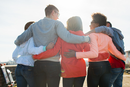 multiracial family: tourism, travel, people, leisure and teenage concept - group of happy friends hugging and talking on city street from back