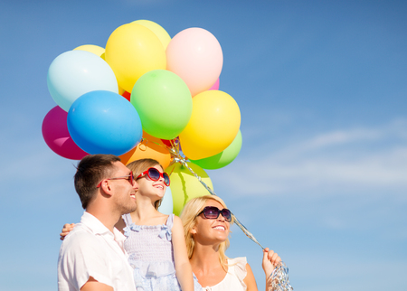 children celebration: summer holidays, celebration, children and people concept - happy family with colorful balloons outdoors