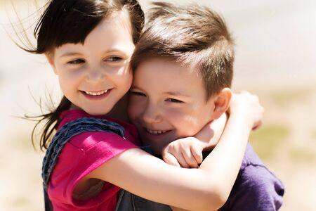 best friend: summer, childhood, family, friendship and people concept - two happy kids hugging outdoors