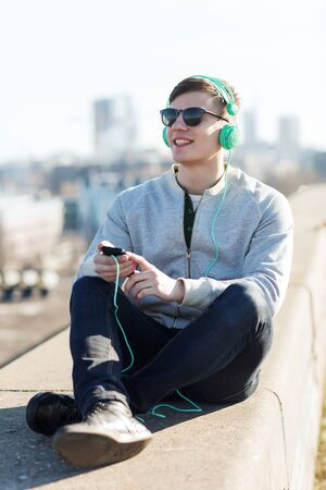 personas escuchando: technology, lifestyle and people concept - smiling young man or teenage boy in headphones with smartphone listening to music outdoors Foto de archivo