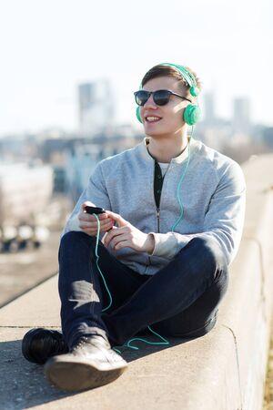 personas escuchando: tecnología, estilo de vida y concepto de la gente - sonriente joven o adolescente en los auriculares con el teléfono inteligente escuchar música al aire libre