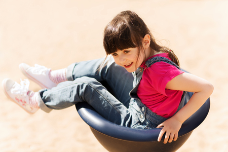summer, childhood, leisure and people concept - happy little girl sitting in rotating chair on children playground