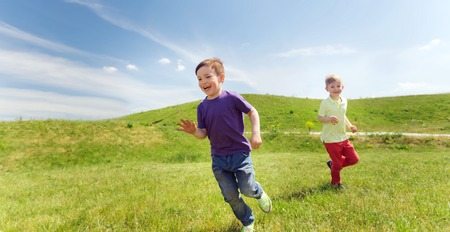 summer, childhood, leisure and people concept - happy little boys playing tag game and running outdoors on green field