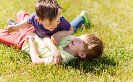 concetto di estate, infanzia, tempo libero e persone - ragazzini felici che combattono per il divertimento sul campo verde