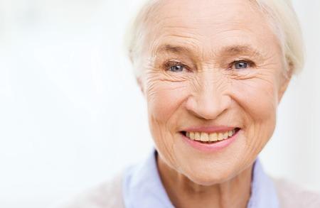 leeftijd en mensen concept - gelukkig lachend senior vrouw gezicht thuis Stockfoto
