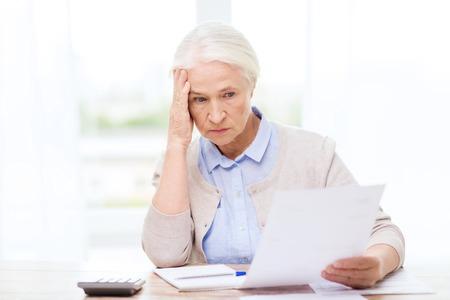 negocio, ahorros, seguros de renta vitalicia, la edad y las personas concepto - mujer mayor con papeles o proyectos de ley y la escritura calculadora en casa