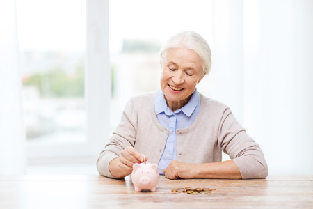 banco dinero: savings, money, annuity insurance, retirement and people concept - smiling senior woman putting coins into piggy bank at home Foto de archivo