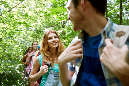 young friends: adventure, travel, tourism, hike and people concept - group of smiling friends walking with backpacks in woods