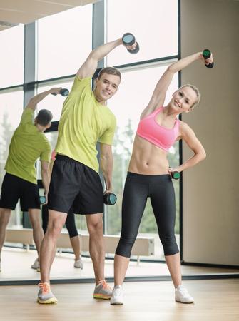 ropa deportiva: deporte, fitness, estilo de vida y concepto de la gente - hombre sonriente y la mujer con pesas de ejercicio en el gimnasio